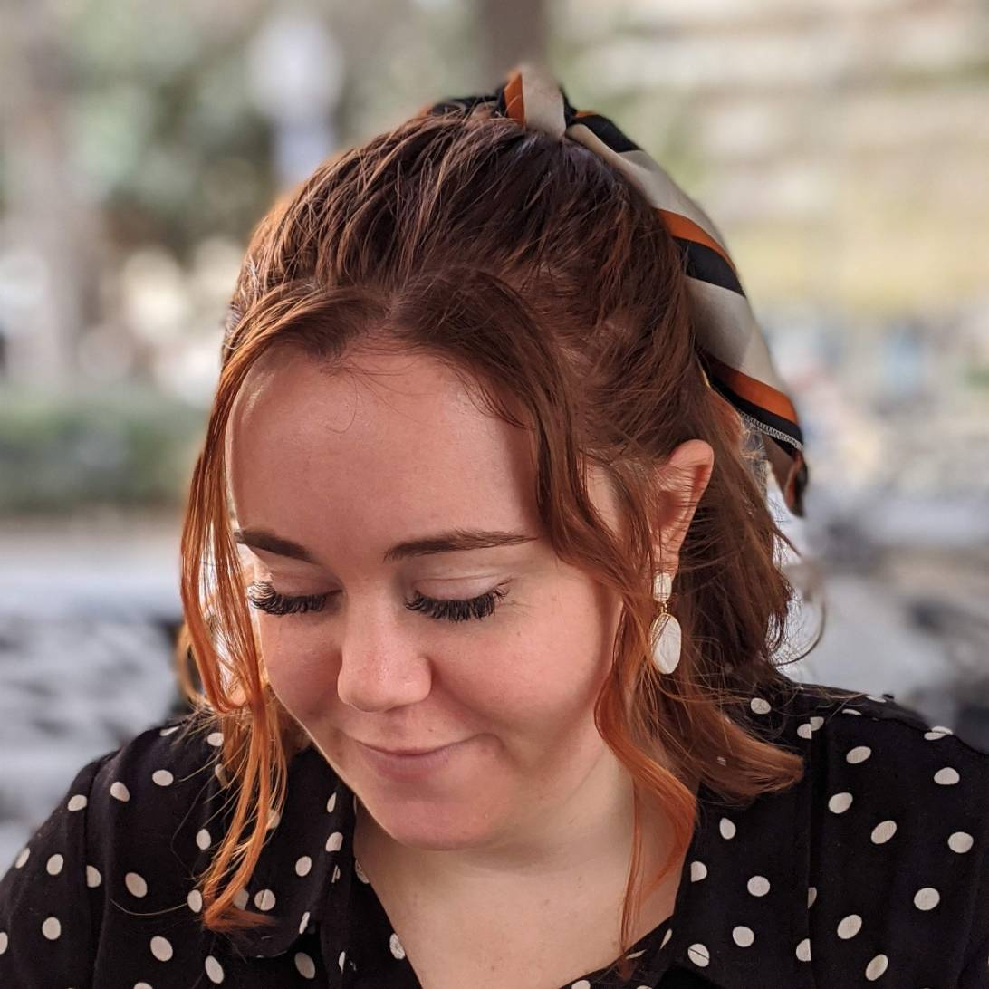 Jessica is pictured looking down off camera. She is wearing a black polka-dot dress and has a bow in her hair.